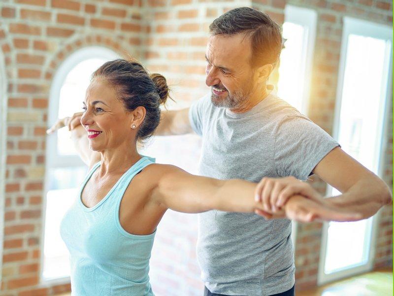 Trainer hilft Frau bei Übung